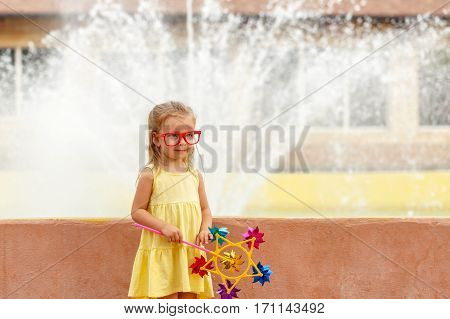 Cute little girl holding a pinwheel in hand. A walk in the summer park near the city fountain. Summer vacation. Outdoor Activities.