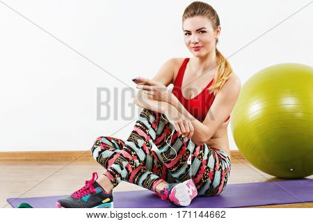 Attractive with light brown hair wearing gray snickers, colorful leggings and red short top sitting on purple matt at gym with mobile phone and fitball, fitness.