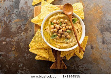Homemade hummus with tortilla chips overhead shot
