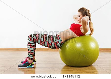Fit girl with light brown hair wearing gray snickers, colorful leggings and red short top doing abdominal exercise with fitball at gym, fitness, white wall and wooden floor.