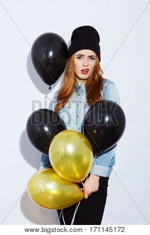 Young teenage red-haired girl with long hair wearing blue shirt and black hat holding balloons, red lips, black manicure, copy space, confused posing, portrait.