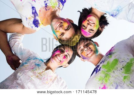young Indian happy friends or couples with heads together in circle celebrating holi festival, with faces coloured with gulal