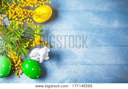 Easter festive still life with branch mimosa eggs and rabbit on blue wooden board top view