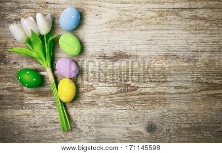 Easter eggs with bunch tulips copyspace on wooden board