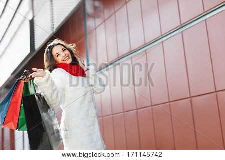 Girl standing with colorful shopping bags near shopping mall and smiling. Beautiful girl with one hand raised holding all bags in it. Putting her another hand on hair. Wearing white coat and red scarf