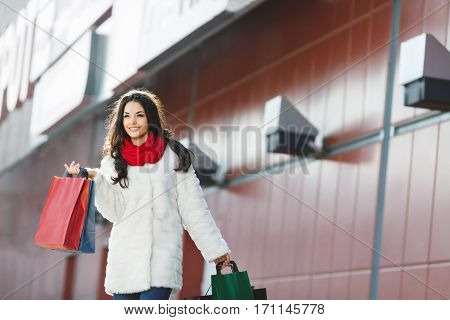 Girl standing with colorful shopping bags near shopping mall, looking aside and smiling. Beautiful girl with one hand raised holding two bags in it. Wearing white coat, red scarf and jeans. Outdoor