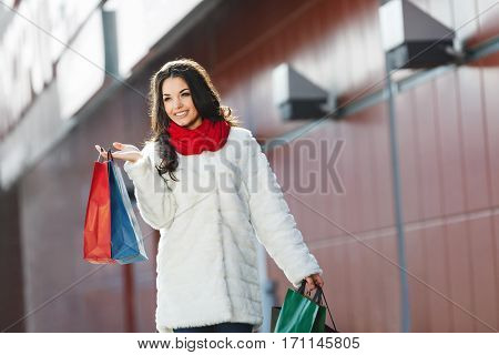 Girl standing with colorful shopping bags near shopping mall, looking aside and smiling. Nice girl with one hand raised holding two bags in it. Wearing white coat, red scarf and jeans. Outdoor