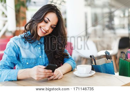 Beautiful girl sitting in cafe in shopping mall, looking at phone and smiling, holding it with both hands. Head turned left a little bit. Colorful shopping bags standing near her on chair.