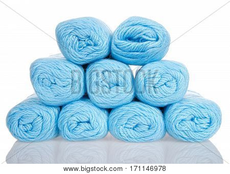 Skeins of powder blue light colored yarn stacked into a pyramid formation on a reflective white surface isolated on a white background.