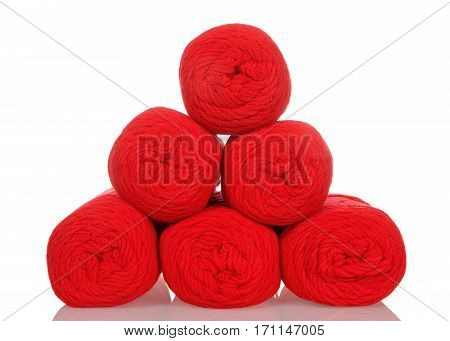 Skeins of red colored yarn stacked into a pyramid formation on a reflective white surface isolated on a white background.