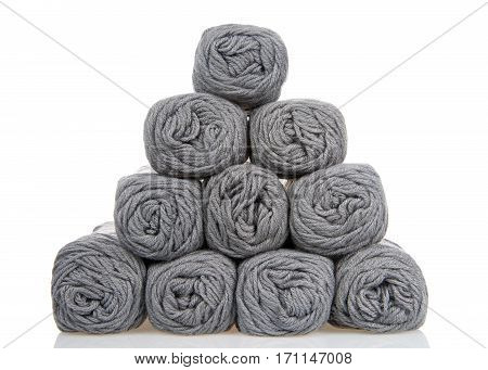 Skeins of gray colored yarn stacked into a pyramid formation on a reflective white surface isolated on a white background.