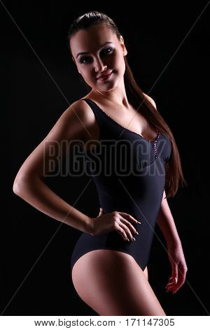 Young athletic girl on a dark background