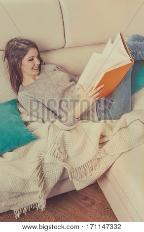 Girl reads a book lying at white soft sofa. Culture lifestyle. Leisure. Young woman reading art literature. Vintage cinematic instagram retro color