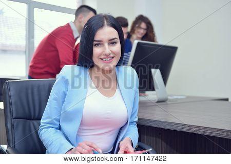 Beautiful girl sitting in office in front of desktop.