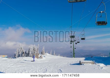Ski lift and chairs on snowy background