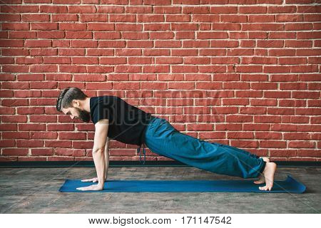 Handsome young man with a beard wearing black T-shirt doing yoga position on blue matt at wall background, copy space, plank.