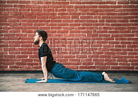 Young man with a beard wearing black T-shirt and blue trousers doing yoga position on blue matt at wall background, copy space, cobra asana, bhujangasana