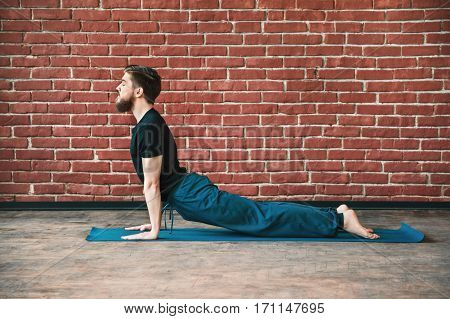Handsome young bearded man with closed eyes wearing black T-shirt doing yoga position on blue matt at wall background, copy space, cobra asana, bhujangasana