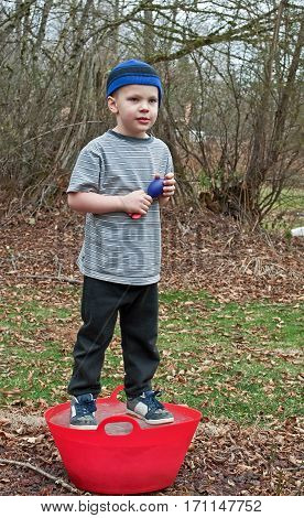 This Caucasian 5 year old boy is playing outside and standing on a red bucket that is frozen solid ice. He's wearing a blue stocking cap black sweat pants and holding a throwing toy. Background intentionally blurred to emphasize subject.