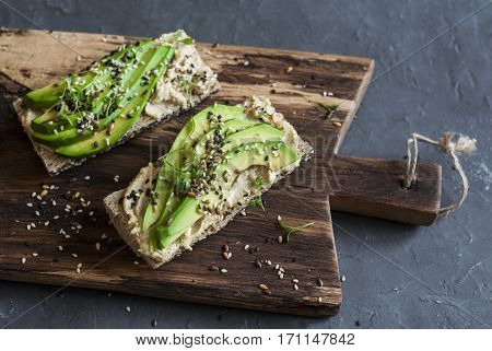 Miso tahini avocado sandwich on wooden cutting board on a dark background. Vegetarian snack