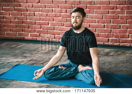 Attractive man with a beard and closed eyes wearing black T-shirt and blue trousers doing yoga position on blue matt at wall background, copy space, portrait, lotus asana, padmasana, meditation