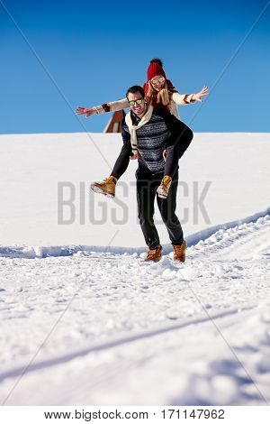 Couple playing in snow. Man giving woman piggyback ride on winter vacation