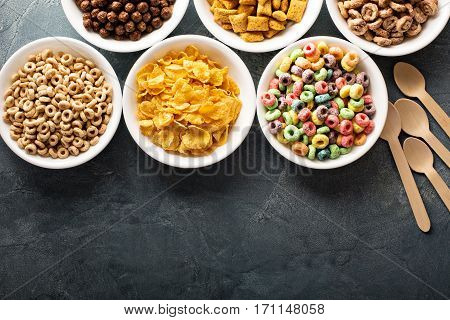 Variety of cold cereals in white bowls, quick breakfast for kids overhead shot with copyspace