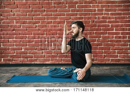 Attractive young man with a beard wearing black T-shirt doing yoga position on blue matt at wall background, copy space, portrait, pranayama exercises.