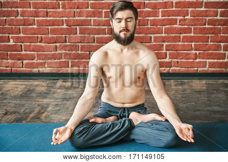 Darkhaired man with closed eyes, dark hair and beard wearing trousers doing yoga position and sitting on blue matt at wall background, position of fingers in mudra, copy space, portrait.