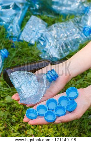 Hand Of Woman With Plastic Bottle And Bottle Caps, Littering Of Environment