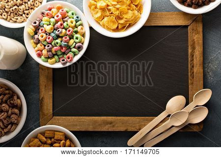 Variety of cold cereals in white bowls around chalkboard, quick breakfast for kids overhead shot with copyspace