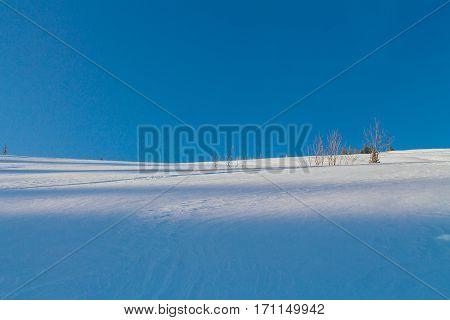 Snow Slope On A Blue Sky Background.