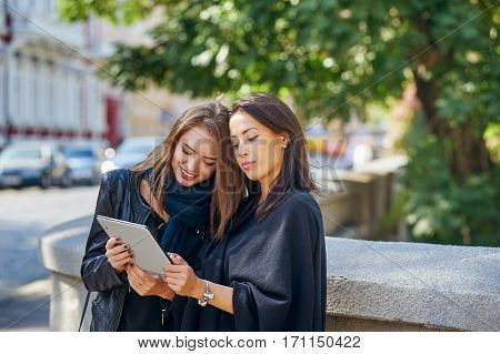 two beautiful young girls look at photos on your tablet , socializing and shopping online