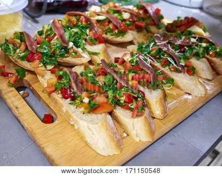 Typical classical Italian Bruschetta with tomatoes herbs and oil on toasted garlic cheese bread on a wooden tray
