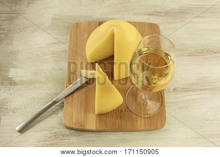 A photo of tetilla, a traditional Spanish soft cow milk cheese, with a slice cut off, and a glass of white wine, on a wooden board