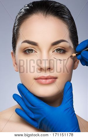 Plastic surgeon drawing dashed line under eye of girl. Beautiful girl. Hands in blue glove holding pencil and face. Plastic surgery, beauty portrait