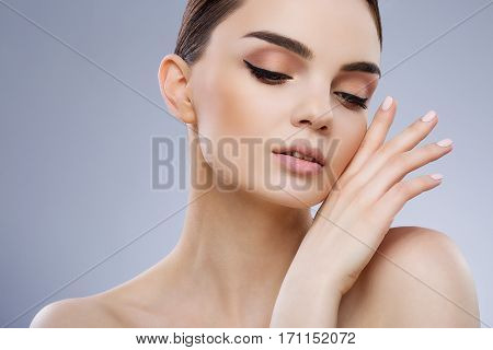 Make up model with brown hair fixed behind, dark eyebrows and naked shoulders looking down and touching her face, portrait, beauty photo.