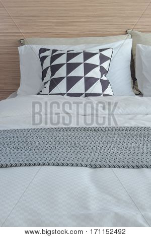 Graphic Pattern Pillow In Black And White Setting On Bed With Wooden Laminated Headboard
