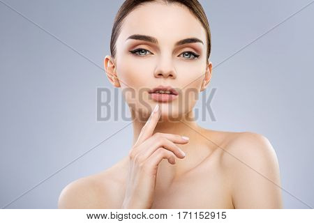 Beautiful model with big blue eyes and perfect make-up looking at camera. Finger touching chin. Beauty portrait, head and shoulders, studio, indoor