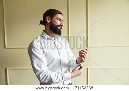 Man buttoning his cuff. Bridegroom looking aside and smiling. Man in white shirt with beard and moustache. Profile. Indoor, studio