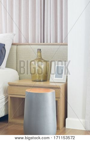 Round Shape Wooden Stool Next To Bedside Table In Bedroom