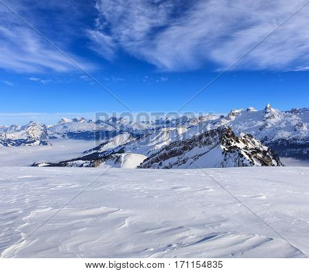 Wintertime view from Fronalpstock mountain in the Swiss canton of Schwyz, summits of the Swiss Alps rising from sea of fog in the background.