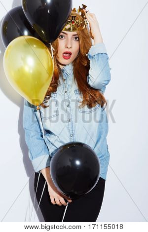 Beautiful teenage red-haired girl with long hair wearing blue shirt and crown holding balloons, red lips, black manicure, copy space, surprised posing.