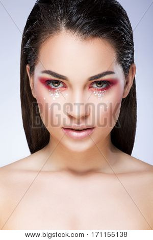 Beautiful girl with bright make-up looking at camera. Eyelids colored in red with little glittering stars. Loose hair. Beauty portrait, head and shoulders, studio