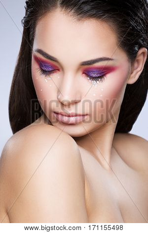 Girl with closed eyes. Bright make-up, eyelids colored in red and purple with little glittering stars. Loose hair. Beauty portrait, head and shoulders, studio