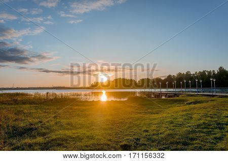 Evening lights of orange sunset over lake in a Valday region village at early spring, Russia. Outdoor nature landscape with sun goes down the lake and lights reflection in calm water near grass meadow