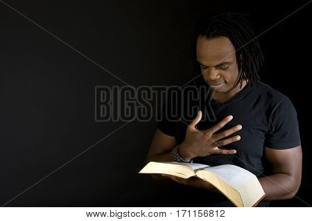 African American man reading a bible isolated on black.