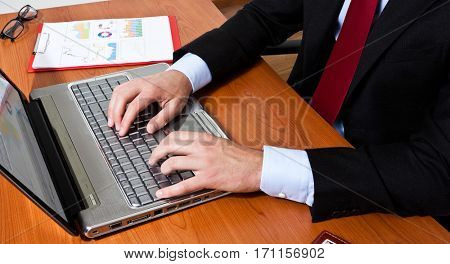 Businessman using a laptop computer on his desk