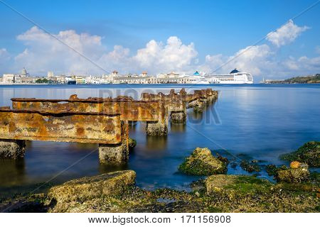 View of the Bay of Havana and the Old Havana skyline with a rusty iron pier on the foreground