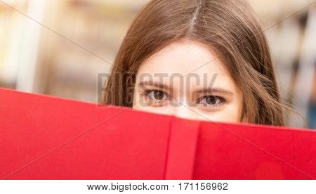 Student looking from behind a book
